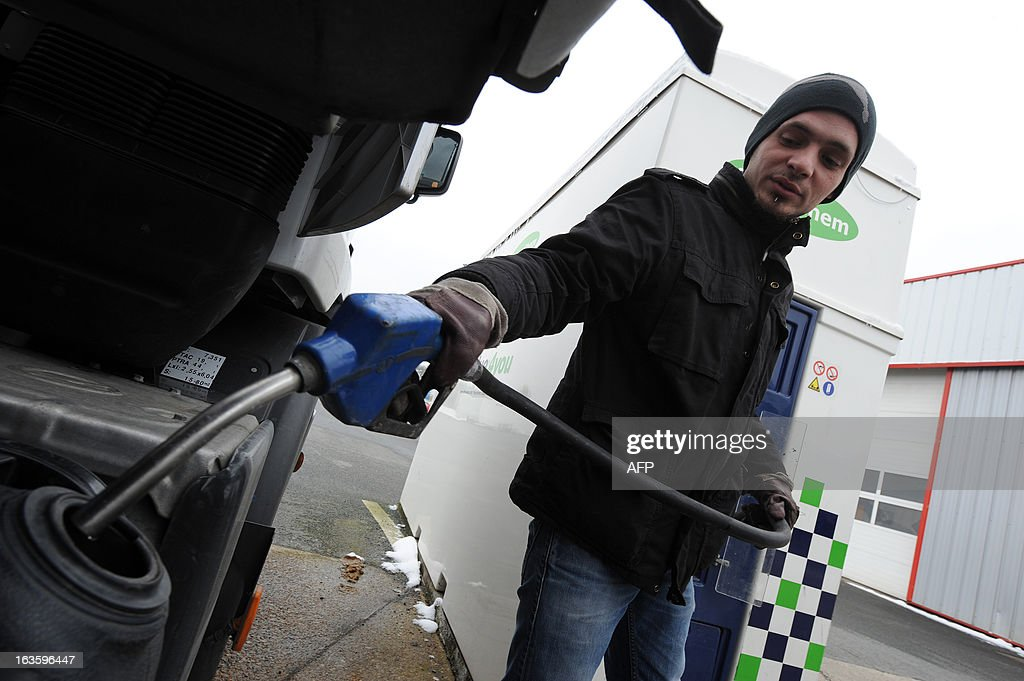 A truck driver fills the tank of his trunk with 'AdBlue,' an additive for reducing emissions of fine particles trucks, at the Transport Robineau company in Soulitre, western France, on March 12, 2013.