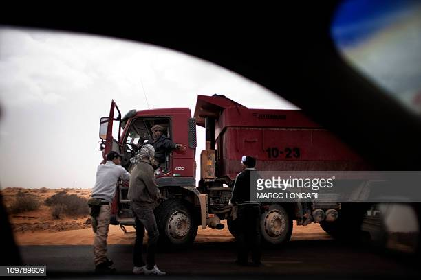 A truck driver gestures towards rebels shooting at the tyres of his lorry as they suspect him of carrying loot at the main point in the rebel held...