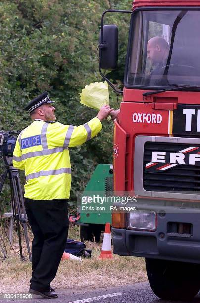 A truck driver hands a bunch of flowers to a police officer to add to those already beside the A29 in Pulborough West Sussex where the body of...