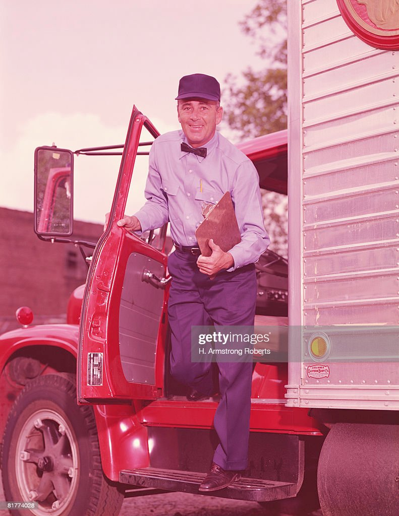 Truck driver holding clipboard, getting out of cab of truck. (Photo by H. Armstrong Roberts/Retrofile/Getty Images) : Stock Photo