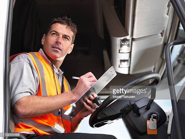 Truck driver makes notes in truck cab