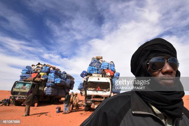 A truck driver poses near a fully loaded trucks in Madama near the border with Libya on January 1 2015 French Defence Minister JeanYves Le Drian paid...