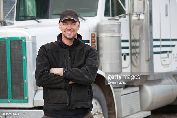 A truck driver posing in front of his truck