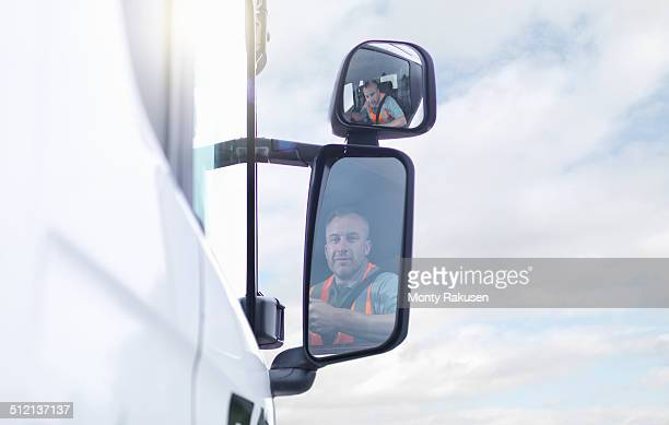 Truck driver reflected in wing mirror