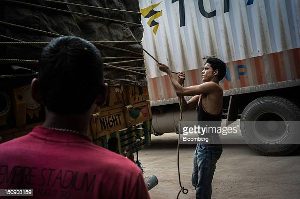 A truck driver secures the tarpaulin on a truck parked at the Transport Corporation of India Ltd's TCIXPS hub in Ambala Haryana India on Monday Aug 6...