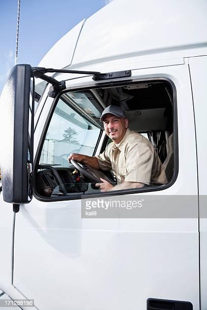 Truck driver sitting in cab of semi-truck