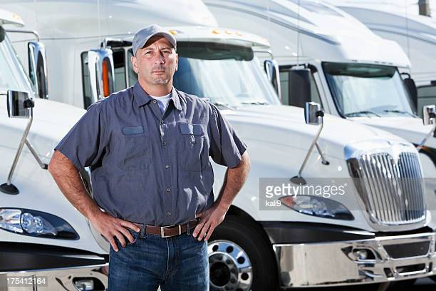 Truck driver standing in front of big rigs