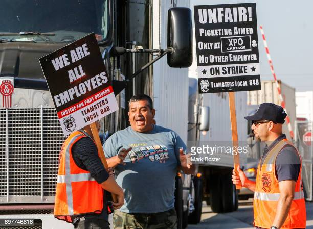 A truck driver trying to exit the XPOLogistics yard in Commerce argues with striking truck drivers and workers walking the picket line over the delay...