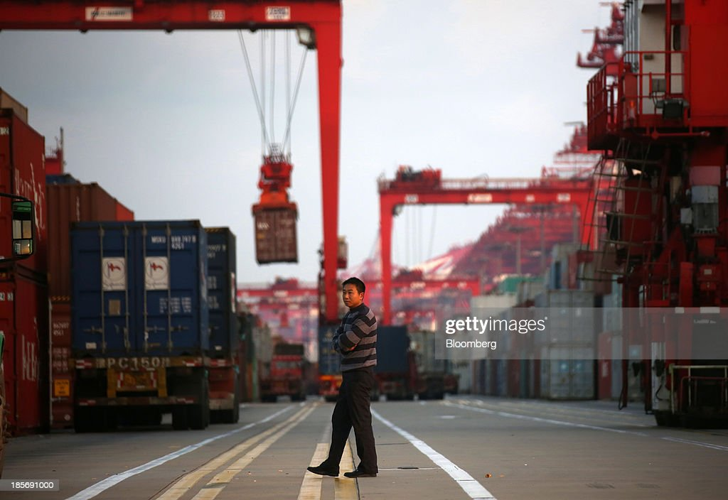 A truck driver walks past a shipping container being moved at the Yangshan Deep Water Port, part of China (Shanghai) Pilot Free Trade Zone's Yangshan free trade port area, in Shanghai, China, on Wednesday, Oct. 23, 2013. The area is a testing ground for free-market policies that Premier Li Keqiang has signaled he may later implement more broadly in the world's second-largest economy. Photographer: Tomohiro Ohsumi/Bloomberg via Getty Images