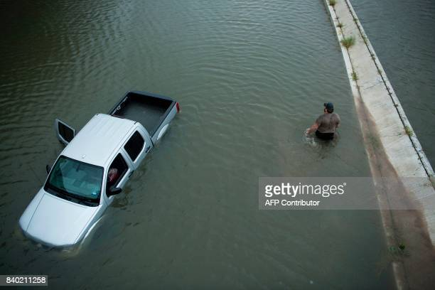 TOPSHOT A truck driver walks past an abandoned truck while checking the depth of an underpass during the aftermath of Hurricane Harvey August 28 2017...