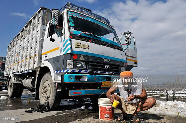 A truck driver wash his face as trucks are stranded at SrinagarJammu national highway due to land slide in Qazigund near Jawhar Tunnel on March 18...
