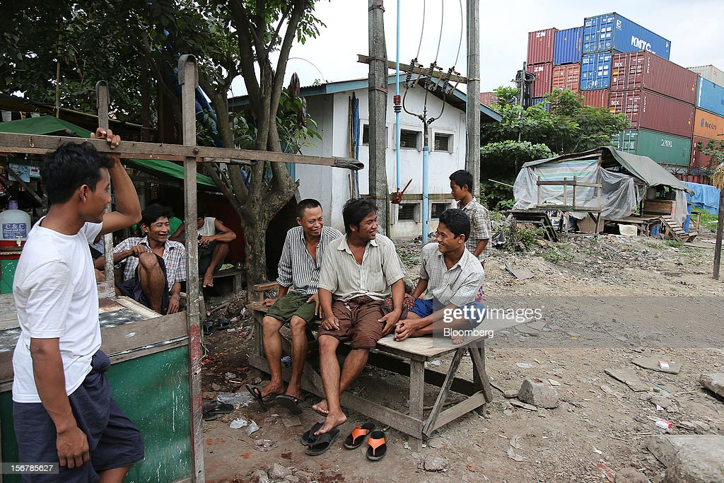 Truck drivers chat at a shipping container depot in Yangon, Myanmar, on Tuesday, Nov. 20, 2012. Myanmar's growth outlook has improved 'substantially' amid political reforms, which are expected to lead to a large influx of foreign investment, the Organization for Economic Cooperation and Development (OECD) said on Nov. 18. Photographer: Dario Pignatelli/Bloomberg via Getty Images