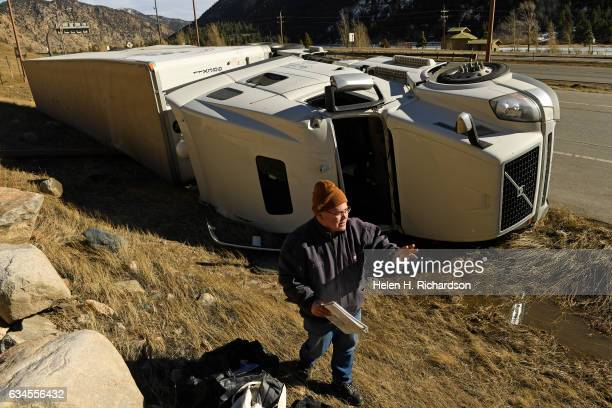 Truck drivers John Minick gathers items in around their semitruck after it blew over from high winds along westbound I70 on roads on February 10 2017...