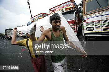 Truck drivers shield themselves in the monsoon rain on July 4 2006 in Bombay India Truck drivers form part of a high risk group for HIV Aids Their...