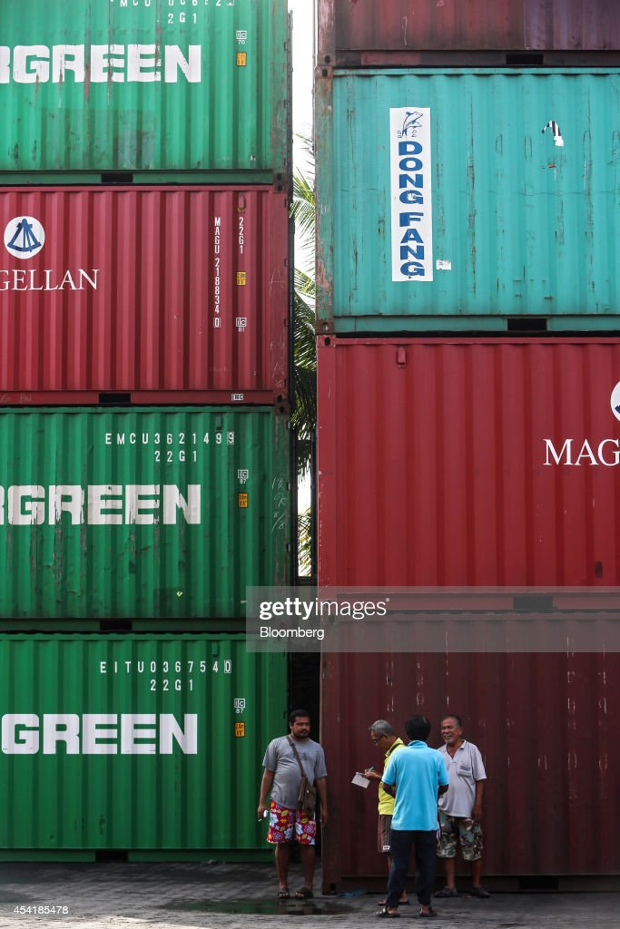 Truck drivers stand talking next to stacked containers at the Custom Global Service Co. container depot in Bangkok, Thailand, on Monday, Aug. 25, 2014. Thailand's trade figures are scheduled for release on Aug. 27. Photographer: Dario Pignatelli/Bloomberg via Getty Images