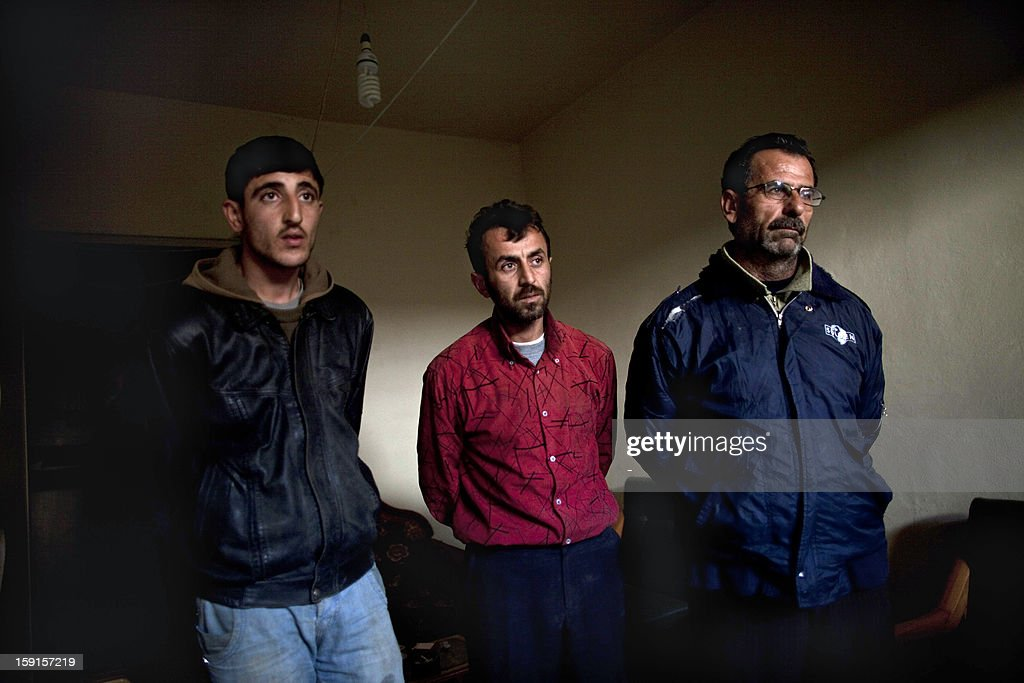Truck drivers who were arrested at a rebel checkpoint for transporting hundreds of bottles of whisky and other banned alcohol hidden in their cargo of water, are seen under arrest at a police station in the Masaken Hanano district of Aleppo, on December 28, 2012. In the heart of Syria's rebel territory, away from the blasts and bullets of the frontlines, another struggle is playing out: one for a new justice system that could shape the future face of the country should the regime fall. The struggle is between ex-regime judges and Islamic jihadists, and at stake is whether the courts apply a modified version of existing Syrian law, or switch to strict sharia law.