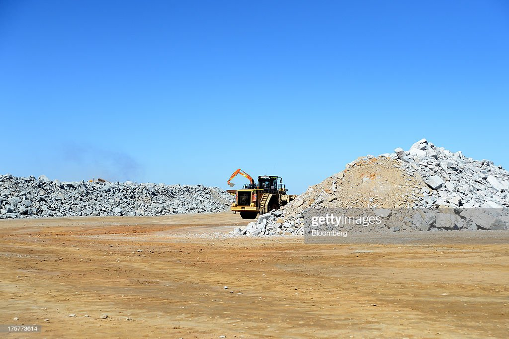 A truck drives between piles of ore at the Norton Gold Fields Ltd. Paddington operations 35 kilometers north-west of Kalgoorlie, Australia, on Wednesday, Aug. 7, 2013. Norton, the Australian producer controlled by China's Zijin Mining Group Co., is seeking further acquisition targets as falling prices cut the value of mines. Photographer: Carla Gottgens/Bloomberg via Getty Images