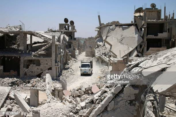 A teuck drives down a destroyed street in a rebelheld area in Daraa on July 19 as civilians started to return to the area following the July 9...