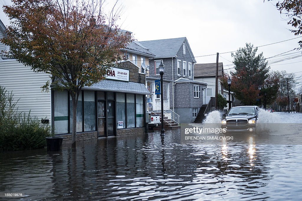 A truck drives down a flooded street after water levels lowered October 30, 2012 in Little Ferry, New Jersey. Hurricane Sandy which hit New York and New Jersey left much of Bergen County flooded and without power. AFP PHOTO/Brendan SMIALOW