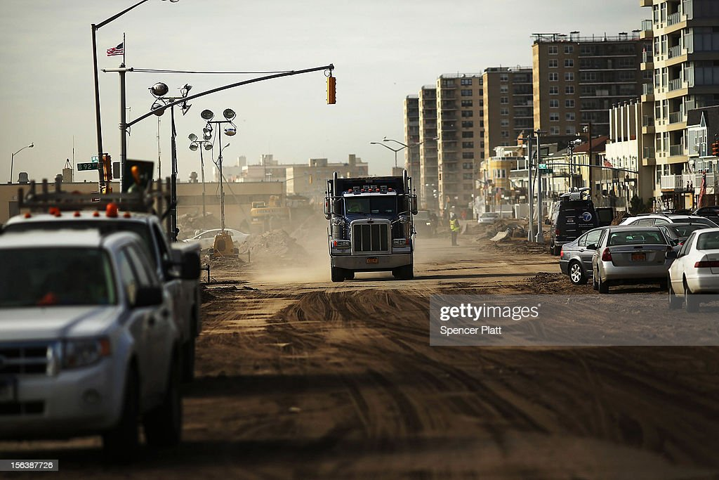 A truck drives down a sand and dirt street while working in the clean-up in the heavily damaged Rockaway neighborhood where a large section of the iconic boardwalk was washed away on November 14, 2012 in the Queens borough of New York City. Two weeks after Superstorm Sandy slammed into parts of New York and New Jersey, thousands are still without power and heat.