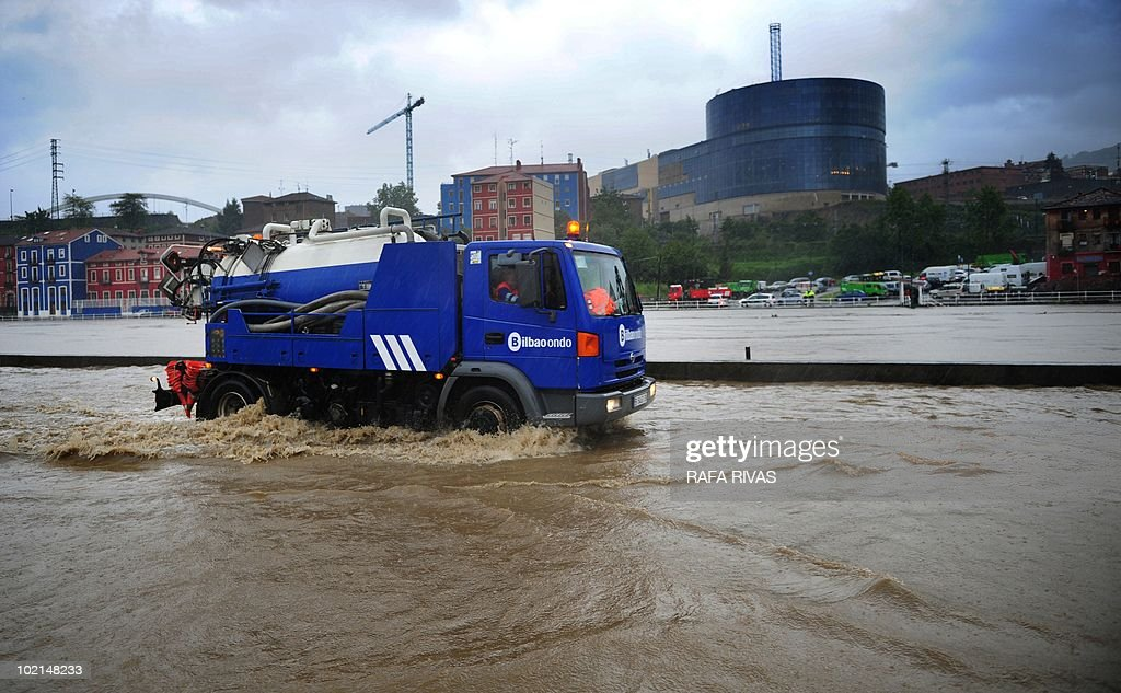 A truck drives on a flooded road along the Nervion river after heavy rains in the northern Spanish Basque city of Bilbao on June 16, 2010. AFP PHOTO/Rafa Rivas