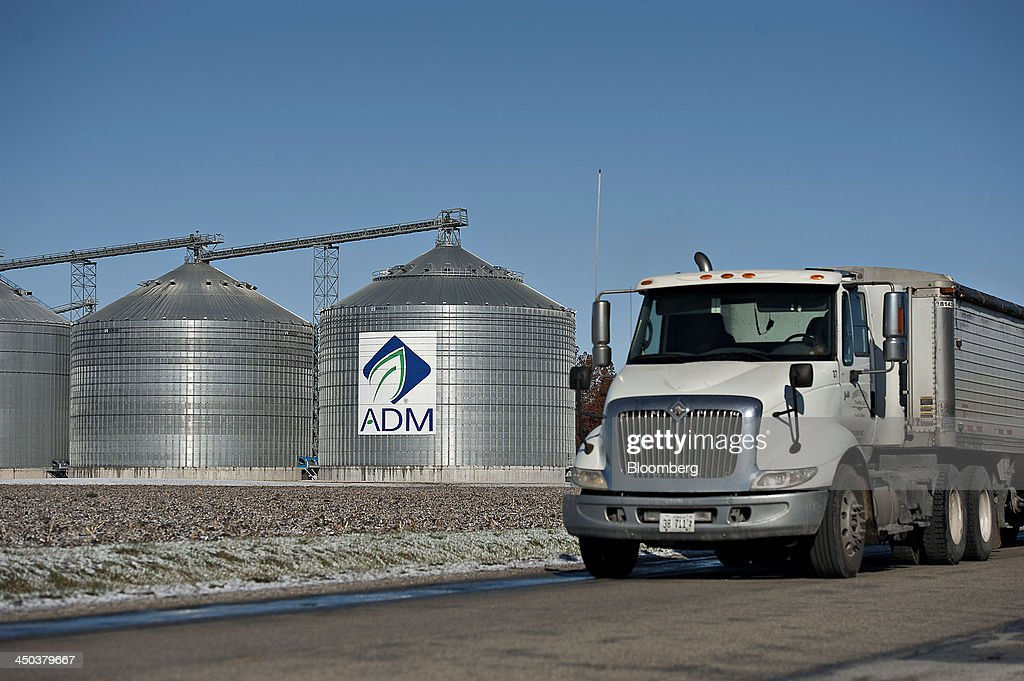 A truck drives on a road near Archer-Daniels-Midland Co. (ADM) signage displayed on the side of a grain storage bin at an ADM grain elevator in Niantic, Illinois, U.S., on Tuesday, Nov. 12, 2013. Archer-Daniels-Midland Co. procures, transports, stores, processes, and merchandises agricultural commodities and products as well as processes oilseeds, corn, milo, oats, barley, peanuts, and wheat. Photographer: Daniel Acker/Bloomberg via Getty Images