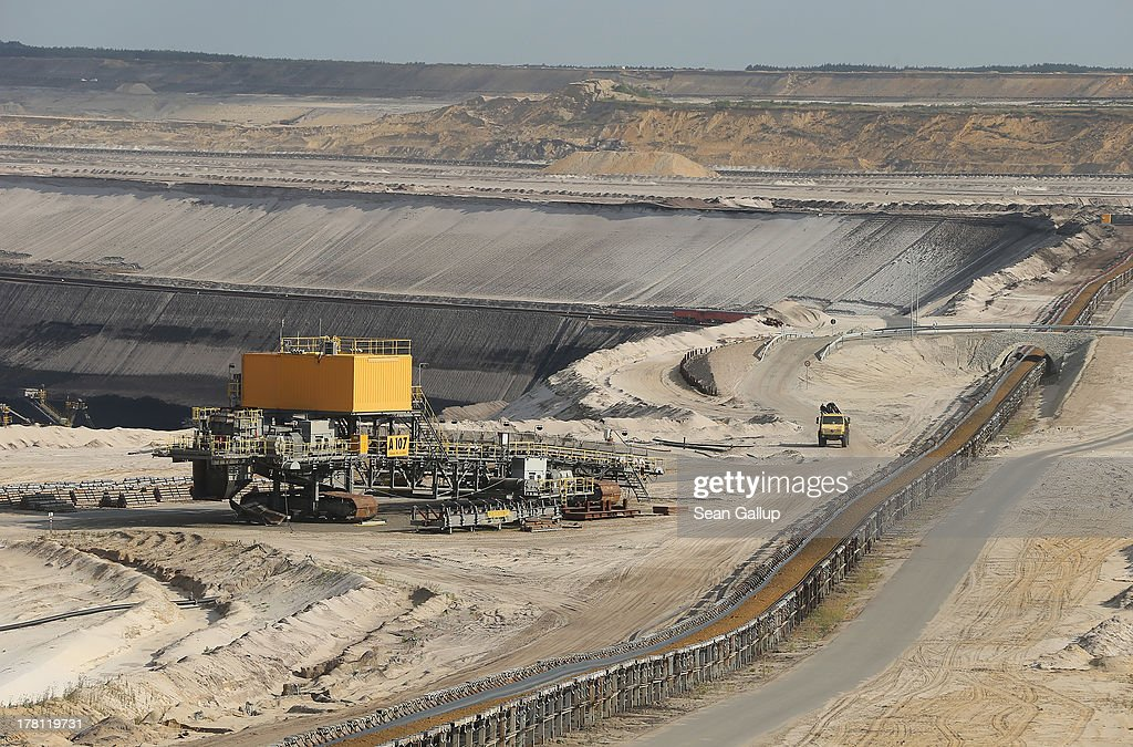 A truck drives past a conveyor belt ferrying topsoil from one end of the Welzow Sued open-pit lignite coal mine to the other on August 26, 2013 near Welzow, Germany. Welzow Sued, operated by Vattenfall, is among the last active open-pit mines in a region known as the Lausitzer Seenland, where dozens of former mines have been turned into lakes. In a development project initiated by state government, other nearby former open-pit mines that once evoked a lunar landscape are being turned into lakes in a long-term rejuvenation effort that is also intended to make the area a viable tourist destination. Mineral residue in the mines, however, is proving a difficult stumbling block that is making many of the new lakes too acidic to sustain marine life in the short term.