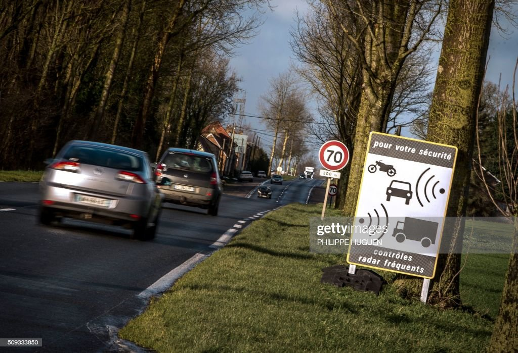 Cars drive past a sign indicating the frequent use of speed cameras on the D939 in Aubigny-en-Artois on February 10, 2016, in the first area in France to be outfitted with 'luring signs'. Eleven signs reading 'For your safety, frequent use of speed cameras' will be installed on a portion of the by-road in the Pas-de-Calais department, but a speed camera will be hidden behind only one of the signs, which will be moved regularly. / AFP / PHILIPPE HUGUEN