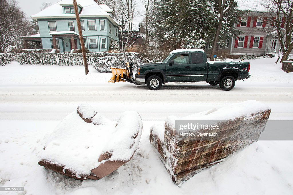 A truck drives past some discarded, snow-covered furniture on December 27, 2012 in Greenfield, Massachusetts. A serious winter storm that caused tornados in the South on Christmas Day swept across the Northeast on Thursday, bringing snow, sleet, rain and causing dangerous travel conditions.