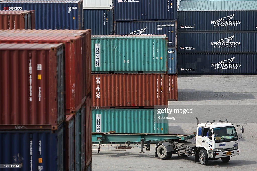 A truck drives past stacked containers at the Port of Bangkok, Thailand, on Monday, Aug. 25, 2014. Thailand's trade figures are scheduled for release on Aug. 27. Photographer: Dario Pignatelli/Bloomberg via Getty Images