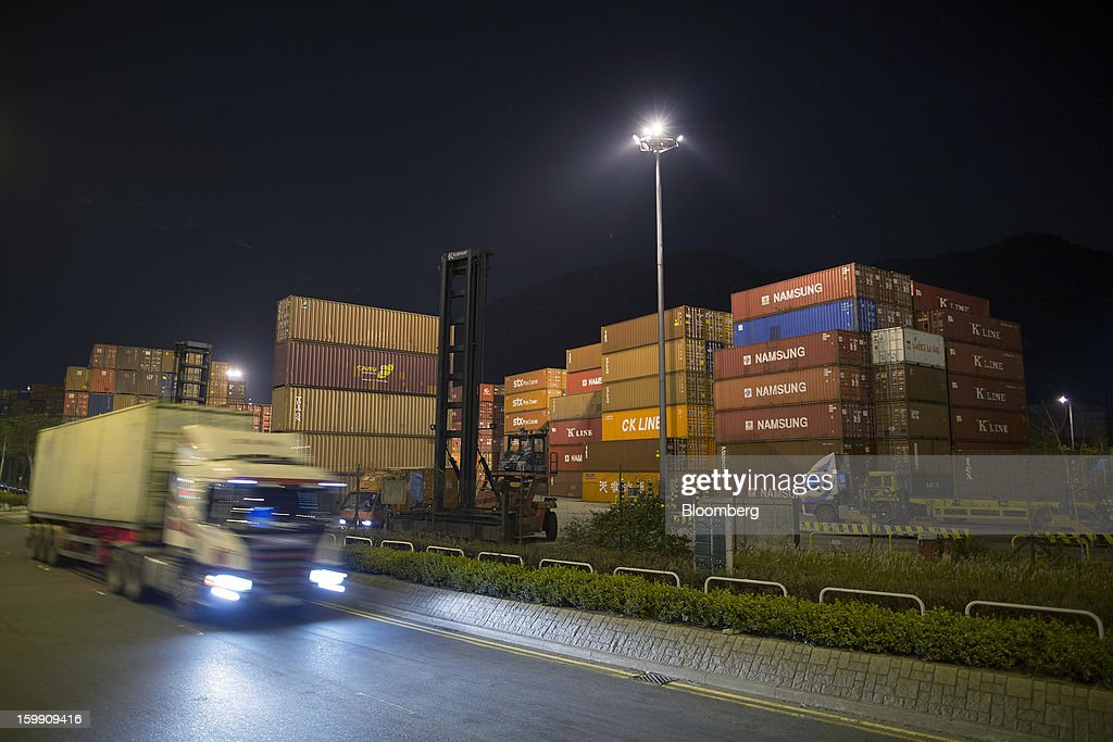A truck drives past stacked shipping containers as they stand at night in the Kwai Tsing Container Terminals in Hong Kong, China, on Tuesday, Jan. 22, 2013. Hong Kong is scheduled to release export figures for December on Jan. 24. Photographer: Jerome Favre/Bloomberg via Getty Images
