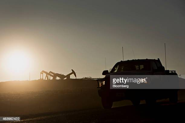 A truck drives past the silhouette of four pumpjacks operating on the site of an oil well outside Williston North Dakota US on Thursday Feb 12 2015 A...