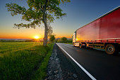 Truck driving on the asphalt road between trees in a rural landscape at sunset