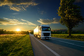 Truck driving on the asphalt road in rural landscape at the golden sunset