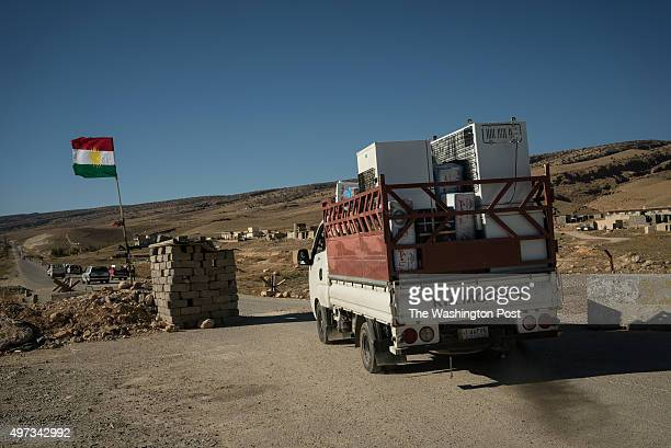 A truck filled with appliances is seen driving out of Sinjar