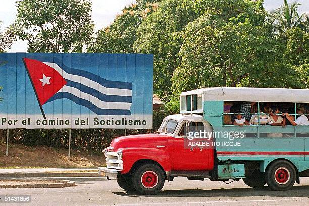 A truck filled with passengers drives past a billboard with the Cuban flag 01 January in Santiago de Cuba marking the 40th anniversary of the...