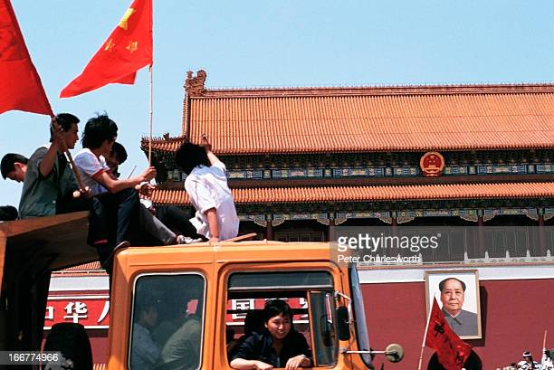 A truck full of protestors Part of a massive march of flagwaving prodemocracy demonstrators drive past the portrait of Mao Tse Tung at the entrance...