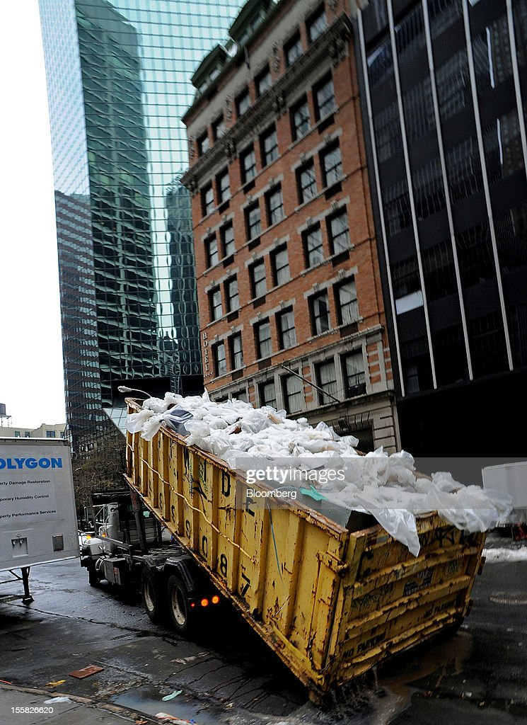 A truck hauls away property damaged by water in the lower Manhattan area of New York, U.S., on Thursday, Nov. 8, 2012. New York-area residents shoveled several inches of snow and airlines prepared to resume flights as the region coped with a nor'easter that slowed the recovery from superstorm Sandy. Photographer: Peter Foley/Bloomberg via Getty Images
