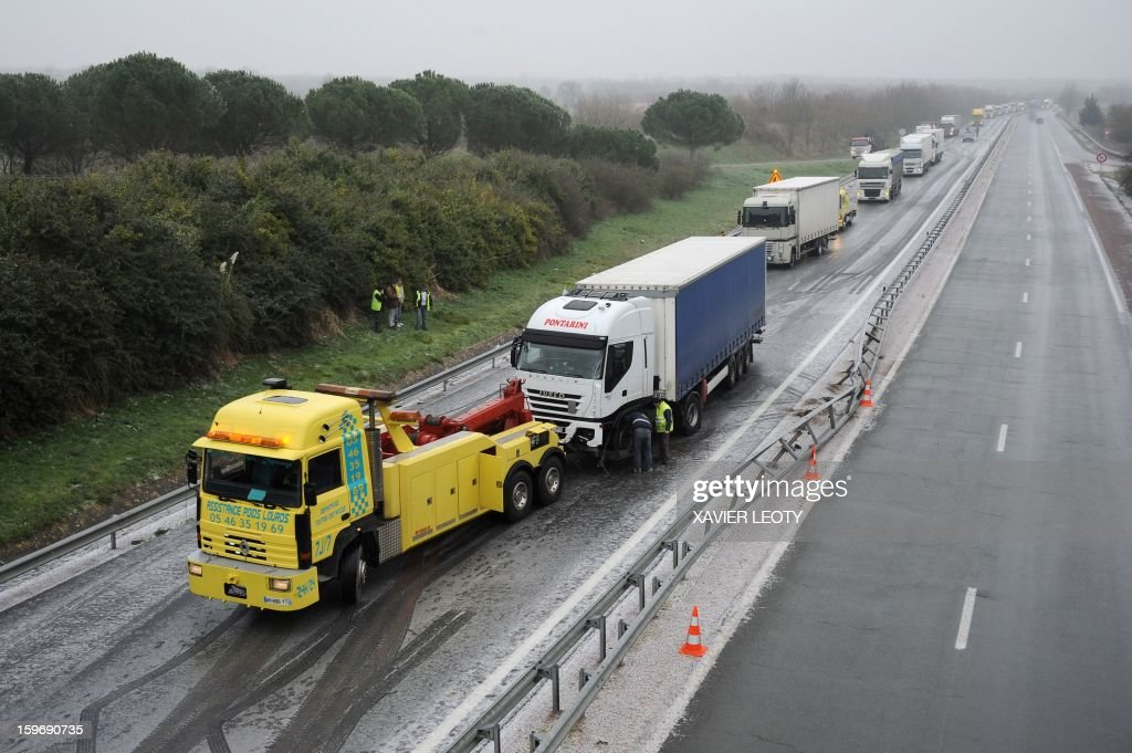 A truck is about to be towed by a tow truck are stuck on an ice-covered road after a crash due to freezing rain, on January 18, 2013 on the RN11 near Ferrieres. Thirty-seven French departments are under medium range (orange) alert due to the inclement weather.