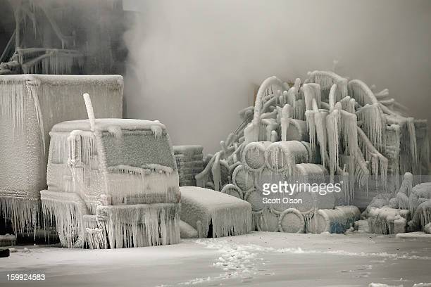 A truck is covered in ice as firefighters help to extinguish a massive blaze at a vacant warehouse on January 23 2013 in Chicago Illinois More than...