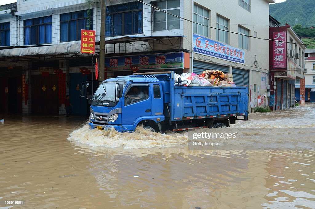 A truck is driven along a flooded street on May 16, 2013 in Jianghua County, China. A round of rainstorms hit South China since Tuesday, leaving 33 people dead and 12 missing.