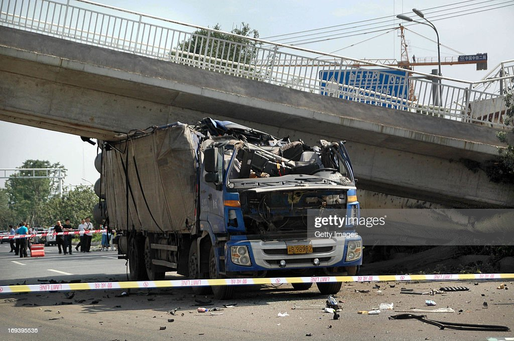 A truck is pinned under a collapsed overbridge on May 23, 2013 in Guiyang, China. An overbridge collapsed when a tank truck crashed and broken a concrete support on west second ring road on Thursday morning, hitting another passing truck and injuring two drivers.