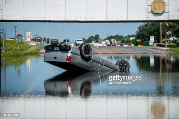 A truck is seen flipped over into floodwater in Port Arthur Texas on September 1 2017 Houston was limping back to life on Friday one week after...