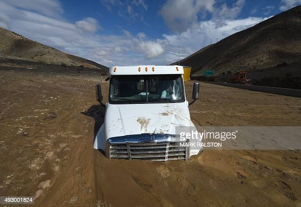 A truck is stuck on a road after being trapped by a mudslide on California Highway 58 in Mojave California on October 16 after torrential rains...