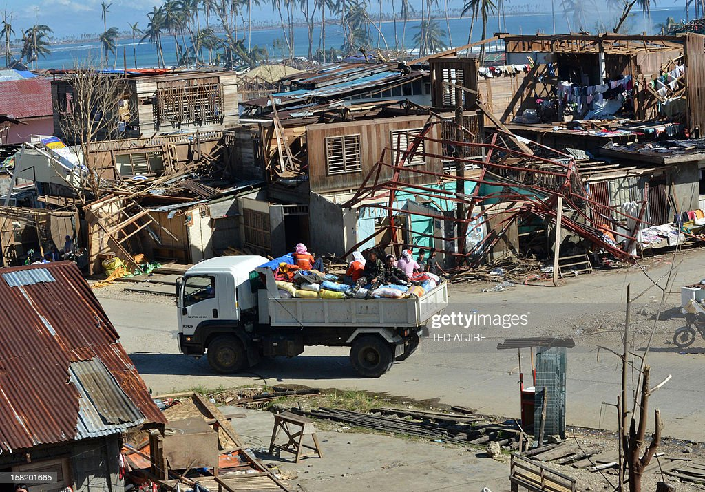 A truck loaded with relief goods passes by destroyed houses in Baganga town, Davao Oriental province on December 11, 2012. The United Nations launched a 65 million USD global appeal on December 10 to help desperate survivors of a typhoon that killed more than 600 people and affected millions in the southern Philippines.