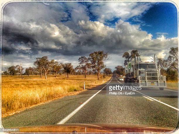Truck Moving On Road Against Cloudy Sky