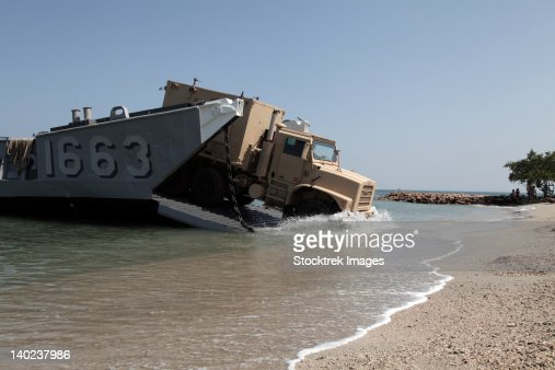 A truck offloads from a landing craft unit. : Stock Photo