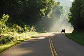 Great travel image of truck on curvy road with beuatiful rays of sunshine streaming through the green, lush trees. By Vicki Dameron