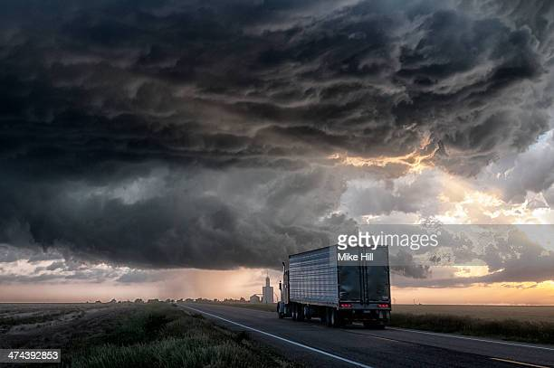 Truck on road with gathering storm clouds