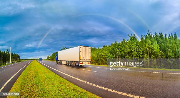 Truck on the highway after the rain driving under the rainbow